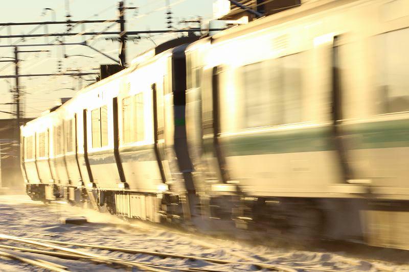 光の中を進む光る銀蛇-朝日浴びて雪を舞い上げ走る列車
