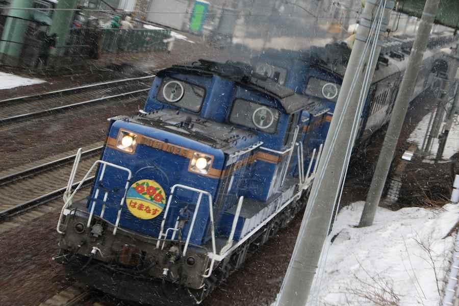 手稲駅付近から雪がちらつく朝の急行はまなす-2016年3月20日